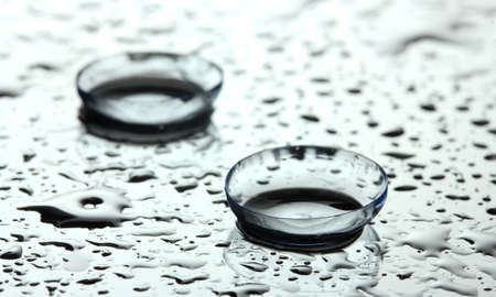 contact lens with drops on grey background photo