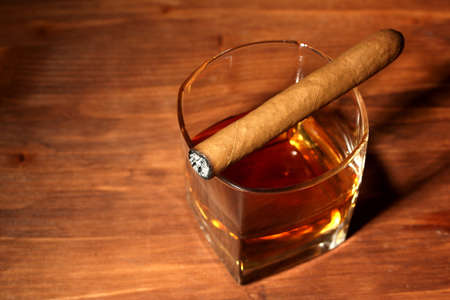 two glass of whiskey and cigar on wooden table photo