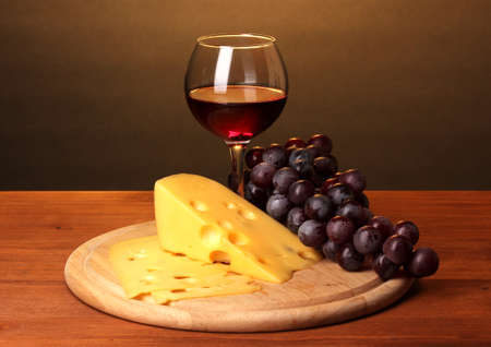 Wine in wineglass and cheese on wooden table on brown background photo