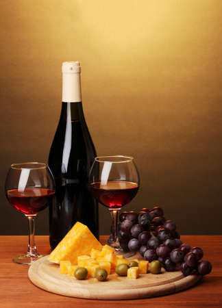 Bottle of great wine with wineglasses and cheese on wooden table on brown background photo