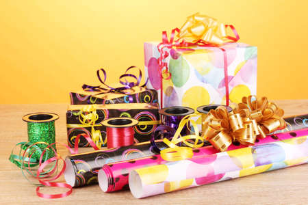 Gigts, paper, ribbon and bows on wooden table on yellow background Stock Photo - 13438145