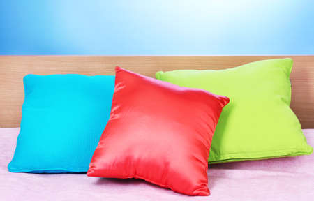 bright pillows on bed on blue background Stock Photo - 13438166
