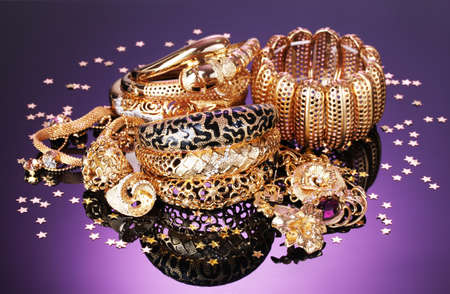 Beautiful golden jewelry on purple background Stock Photo - 13438229