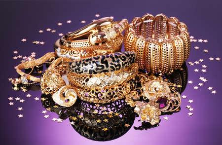 Beautiful golden jewelry on purple background Stock Photo - 13438229