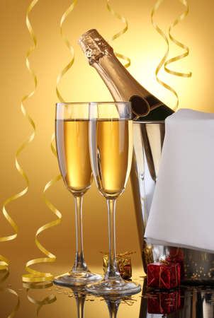 Champagne bottle in bucket with ice and glasses of champagne, on yellow background Stock Photo - 13438101