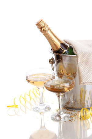 Champagne bottle in bucket with ice and glasses of champagne, isolated on white photo
