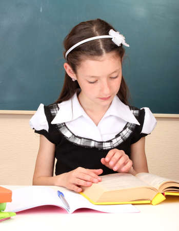 little schoolchild in classroom write in notebook Stock Photo - 13456224