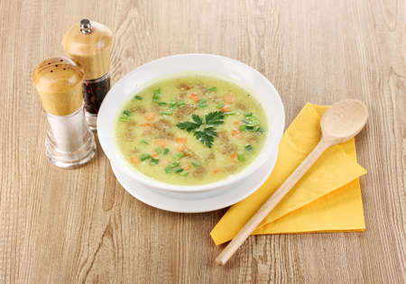 Tasty soup on wooden background photo