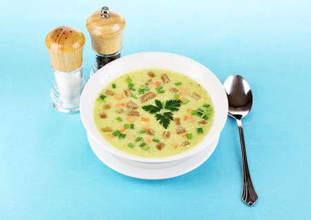 Tasty soup on blue tablecloth isolated on white photo