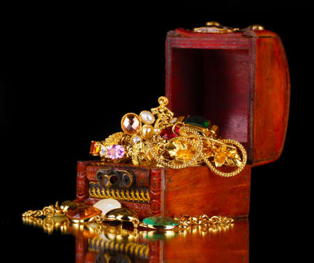 Wooden chest full of gold jewelry on black background photo