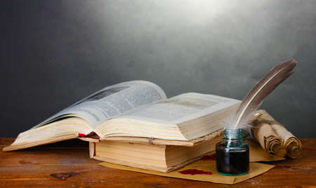 scrool: old books, scrolls, feather pen and inkwell on wooden table on grey background Stock Photo