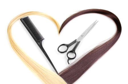 Shiny blond and brown hair with hair cutting shears and comb isolated on white photo