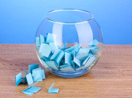 involvement: Pieces of paper for lottery in vase on wooden table on blue background Stock Photo