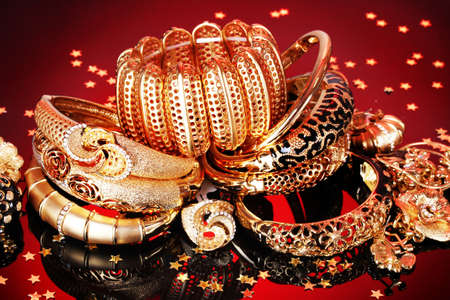 Beautiful golden jewelry on red background photo