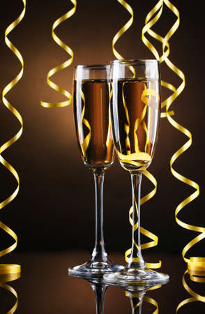 glasses of champagne and streamer on brown background photo