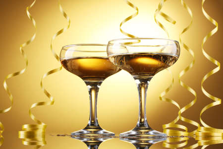 glasses of champagne and streamer on yellow background Stock Photo - 13438855