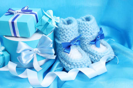 beautiful gifts and baby's bootees on blue silk Stock Photo - 13438921