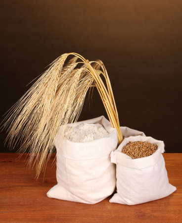 Flour and wheat grain on wooden table on dark background photo