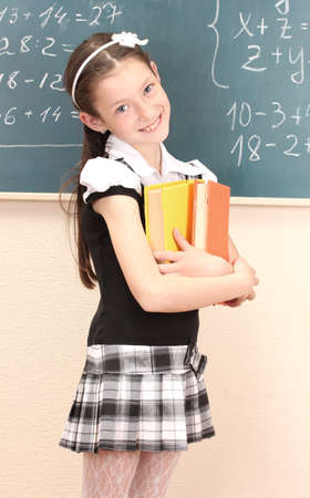 beautiful little girl in school uniform with books in class room photo