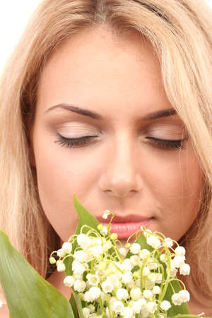 Beautiful young woman with lilies of the valley on white background close-up photo