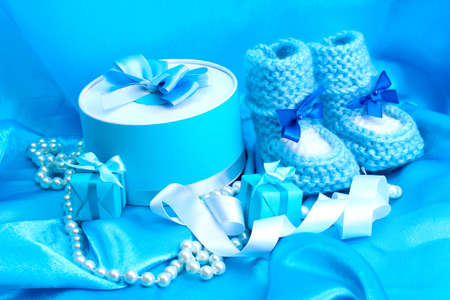 bootees: beautiful gifts and babys bootees on blue silk Stock Photo