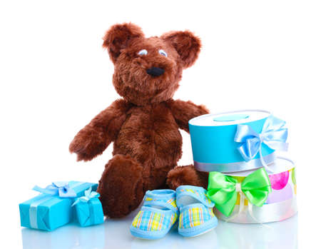 children s feet: beautiful gifts, babys bootees and bear toy  isolated on white