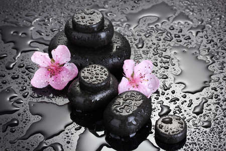 laborer: Spa stones with drops and pink sakura flowers on grey background  Stock Photo