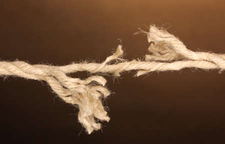 abruption: Breaking rope on brown background