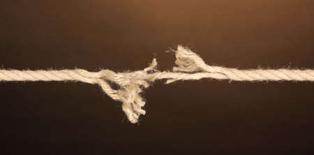 discontinuity: Breaking rope on brown background