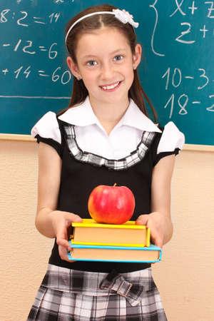 školačka: krásná holčička ve školní uniformě s knihami a apple ve třídě pokoji Reklamní fotografie