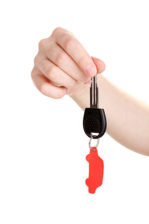 Car key with charm in hand isolated on white photo