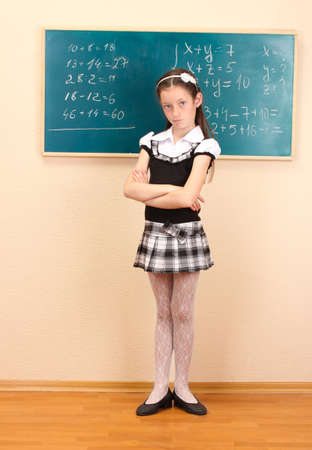 beautiful little girl in school uniform in class room photo