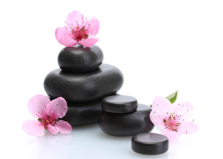 Spa stones and pink sakura flowers isolated on white  photo