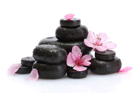 Spa stones with drops and pink sakura flowers isolated on white  photo