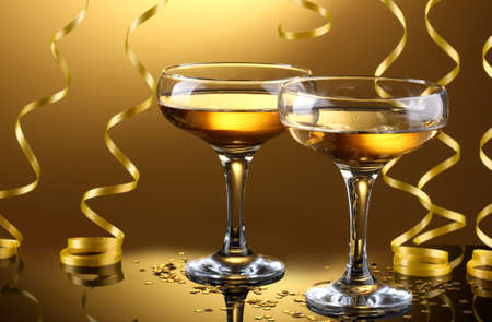 glasses of champagne and streamer on yellow background photo