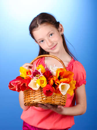 resent: Portrait of beautiful little girl with tulips in basket  on blue background Stock Photo