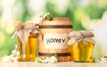 Sweet honey in barrel and jars with acacia flowers on wooden table on green background photo