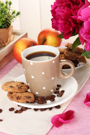 cup of coffee, cookies, apples and flowers on table in cafe photo