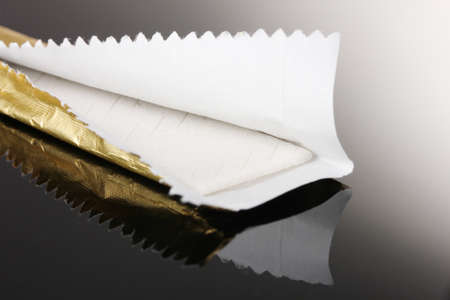 chewing: Chewing gum on the wrapping foil on gray background