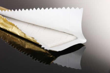 goma de mascar: La goma de mascar en el papel de envolver sobre fondo gris