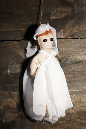 hanged woman: Hanged doll voodoo girl-bride  on wooden background Stock Photo