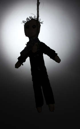Hanged doll voodoo boy-groom on grey background photo