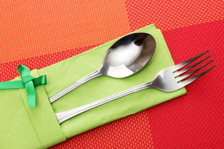 Fork and spoon in a green cloth with a bow on a red tablecloth photo