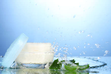 natural cosmetics: Opened jar of cream in water splash on blue background