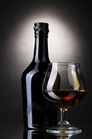 Glass of brandy and bottle on gray background photo