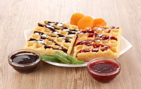 Sweet waffles with jam and chocolate on plate on wooden background photo