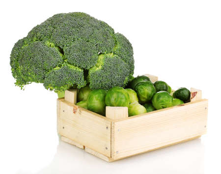 Brussels sprouts in wooden crate and broccoli isolated on white photo