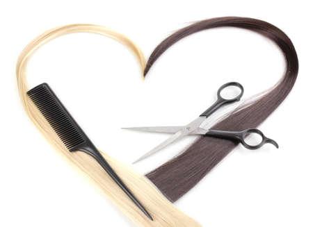El pelo rubio y brillante de color marrón con tijeras de corte de pelo y un peine aislados en blanco Foto de archivo