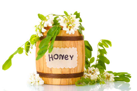 Sweet honey in barrel with acacia flowers isolated on white photo