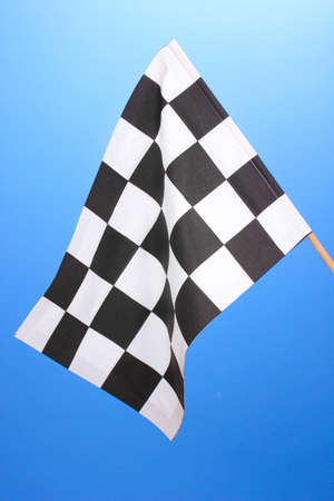Checkered finish flag on blue background photo